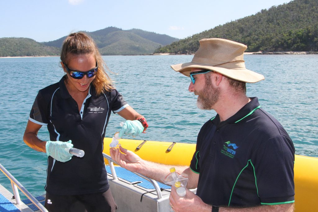 JCU aquatic scientist Jordan Iles shows Victoria Rival De Bouville from Southern Cross Sailing how to take a water sample