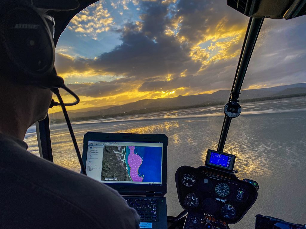 Inside a helicopter cockpit over the sea.